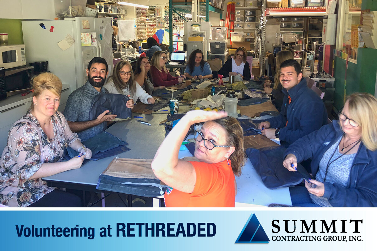 Summit Employees smiling and waving to camera while stitching clothes at a volunteer event