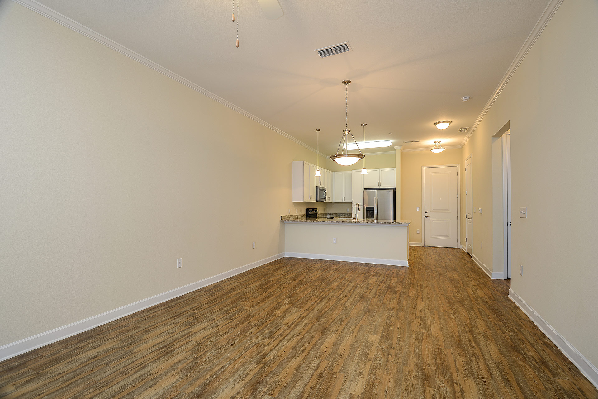 Wooden floor empty unit with kitchen