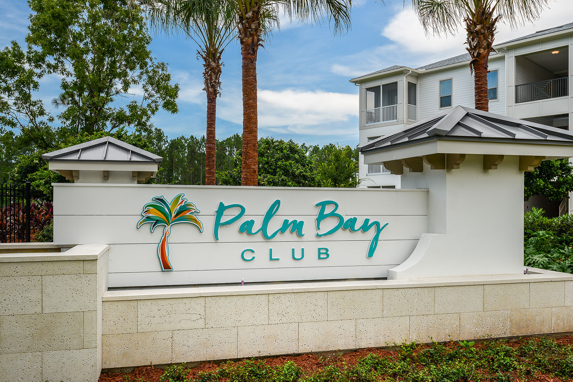 Front sign of Palm Bay Club complex with palm trees