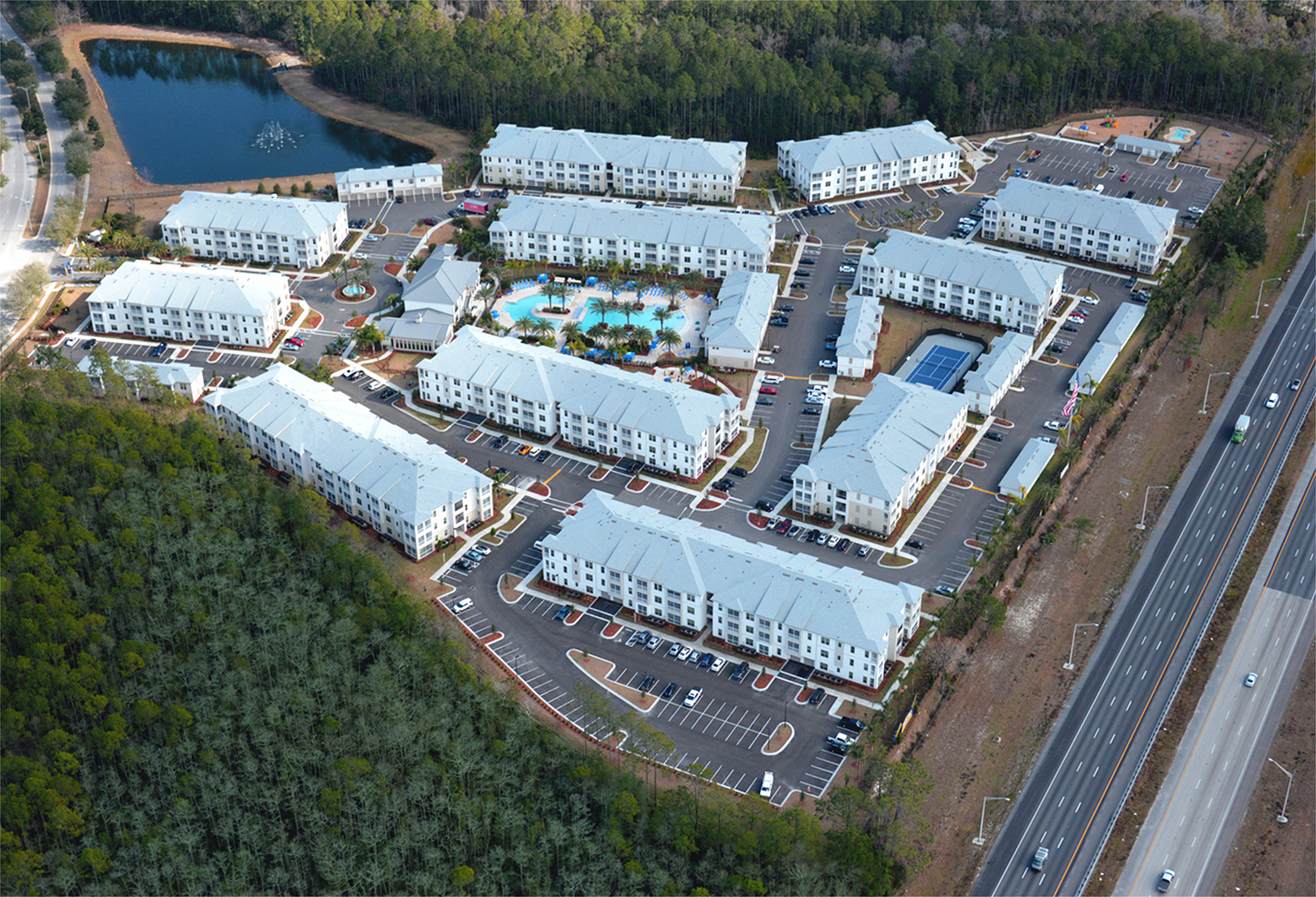 Aerial shot of apartment complex with pool area and palm trees