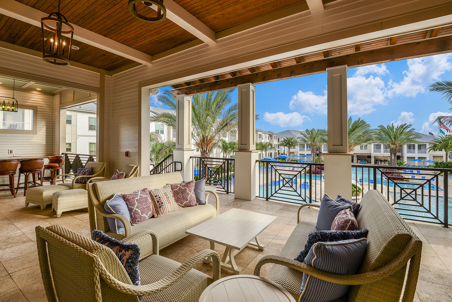 Lounging area of apartment complex with large pool and fancy chairs