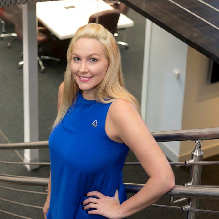 Woman in blue dress with Summit pin smiling to camera on stairs