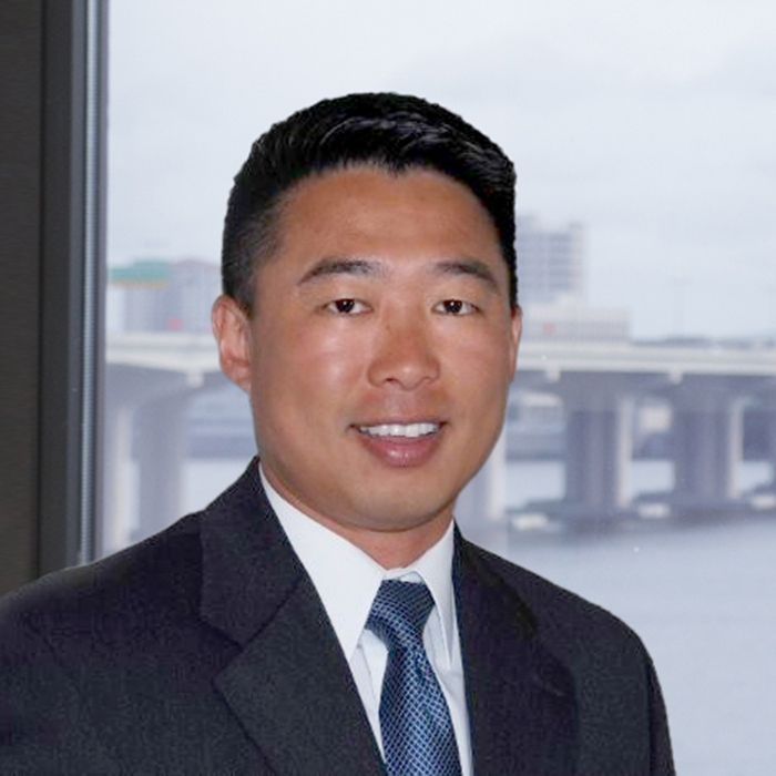 Asian man in suit smiling at camera