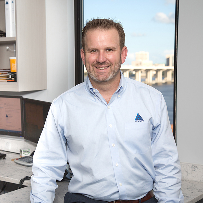 Man in Summit shirt smiling at camera