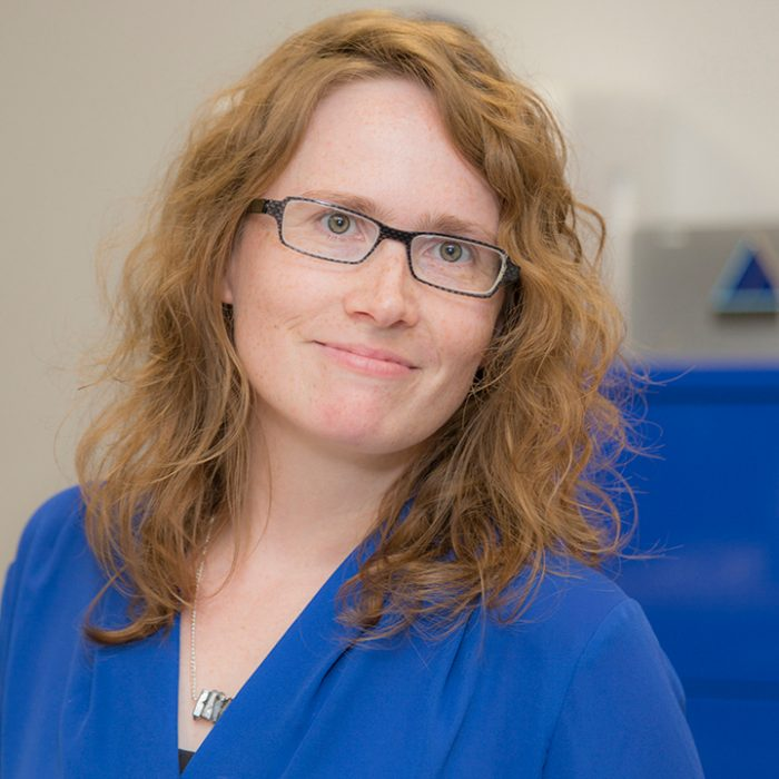 Woman with red hair in blue shirt and glasses smiling