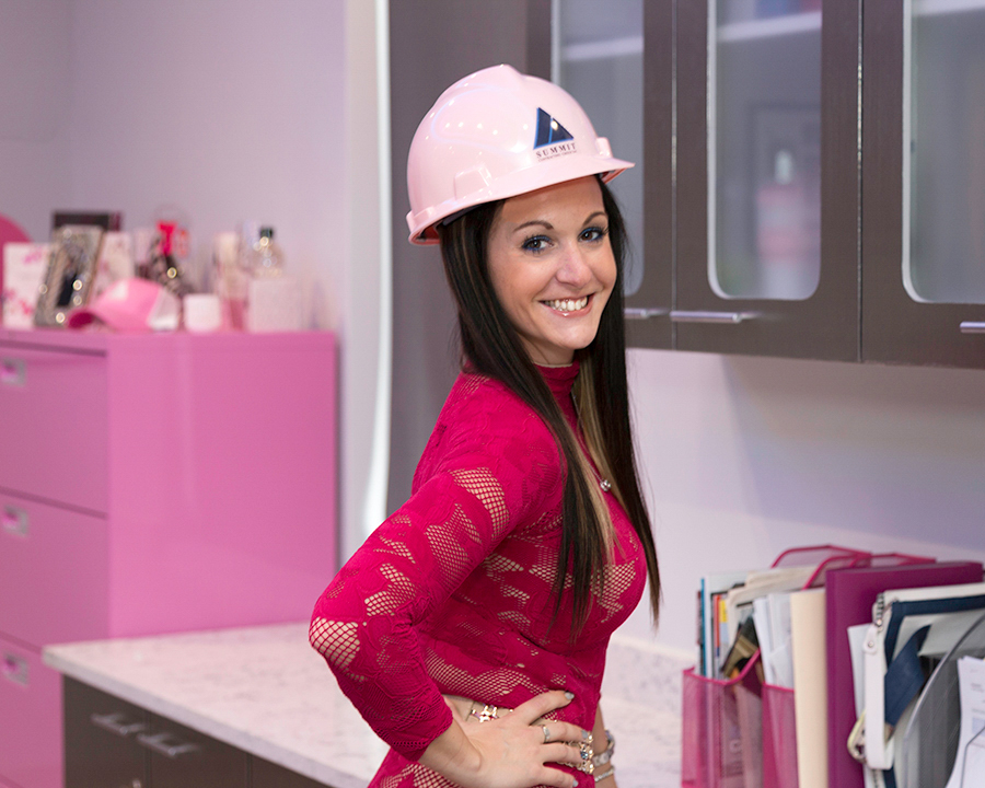 Woman in a pink Summit hard hat smiling and posing