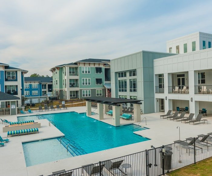 Light blue apartment building with pool area