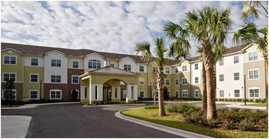 Senior living entrance with palm trees