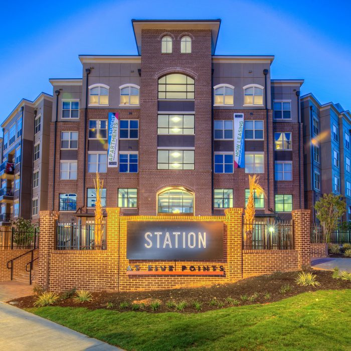 Multi level student housing at night with Station at Five Points sign