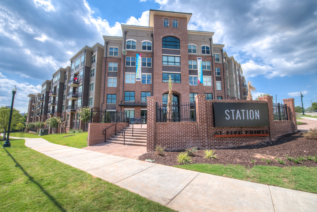 Brick Multi level student housing with Station at Five Points sign