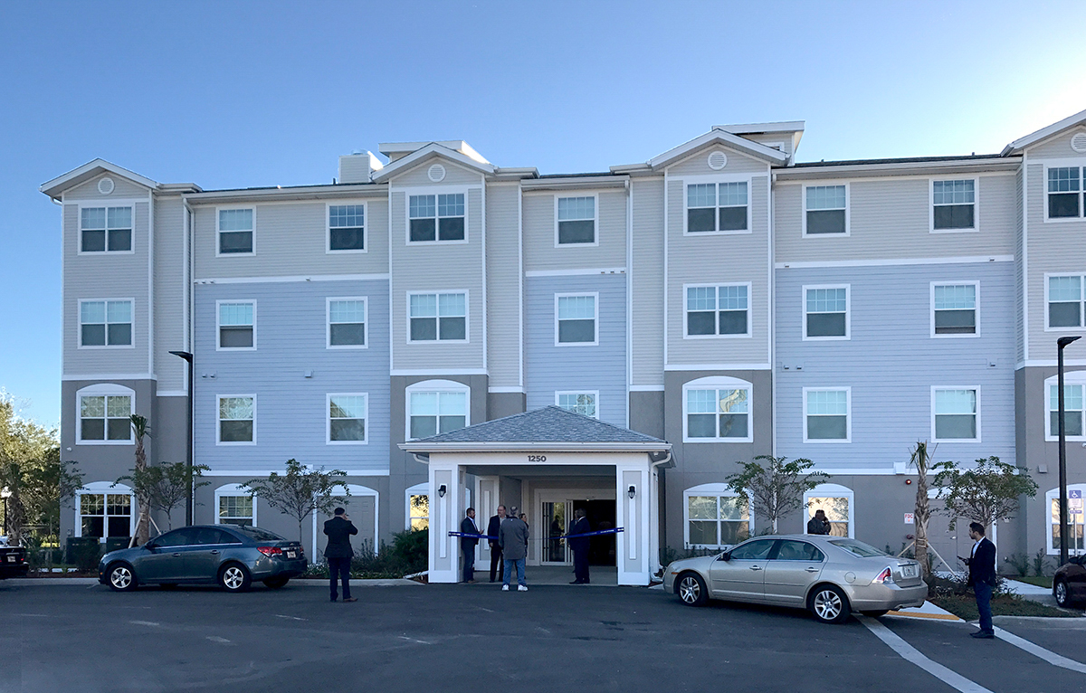 Multi level senior living facility front entrance with people at door