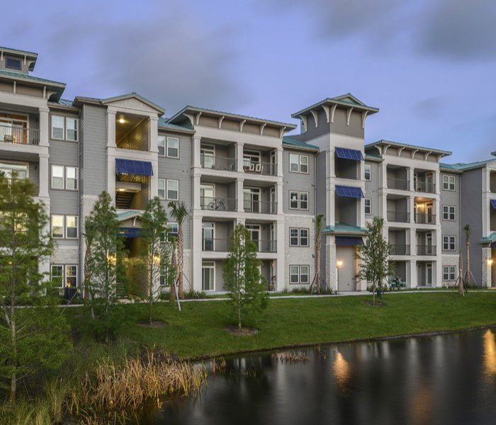 Multi story apartments with porches by small pond