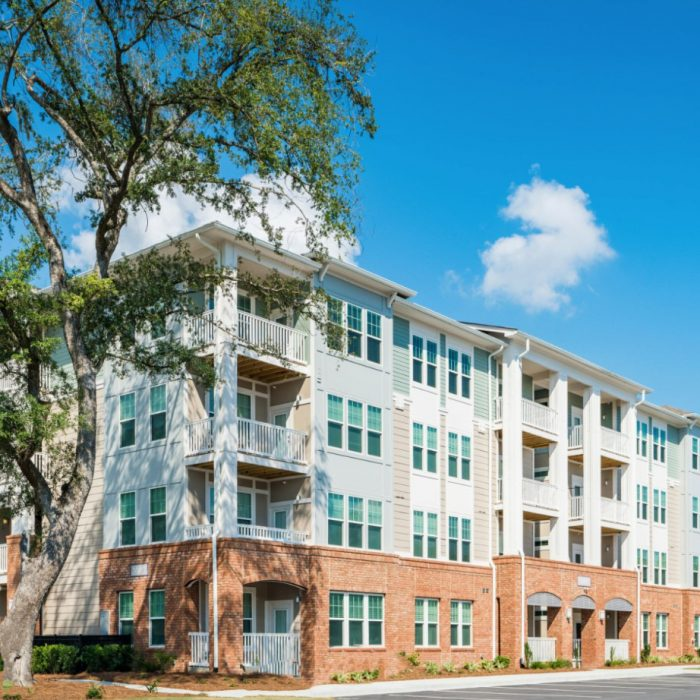 Teal and brown multi story apartment complex angle view with tree