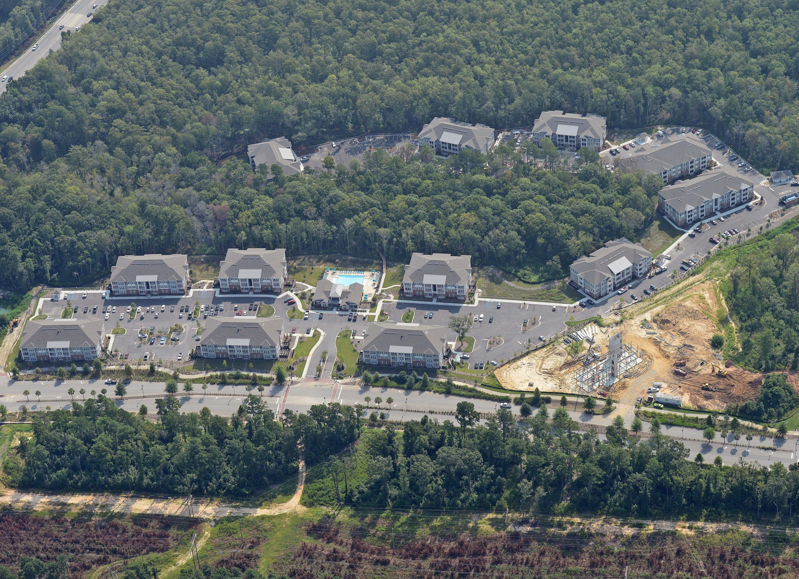 Teal and brown multi story apartment complex aerial view with parking lot