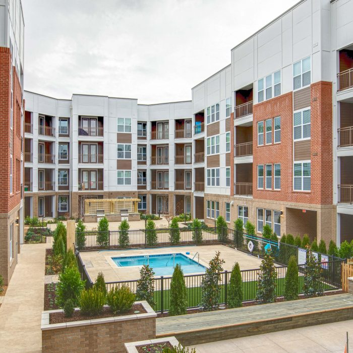 Multi story apartment complex pool area surrounded by plants