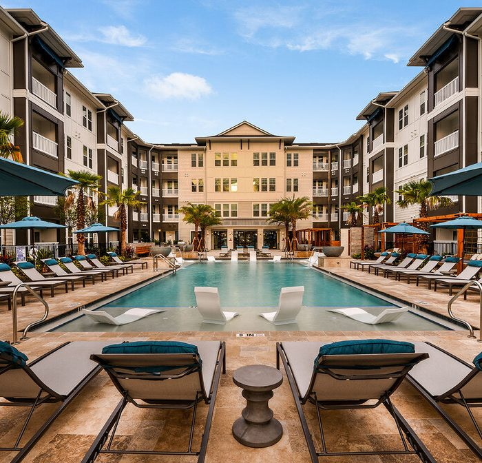 Luxury multi story apartments pool area with lounge chairs