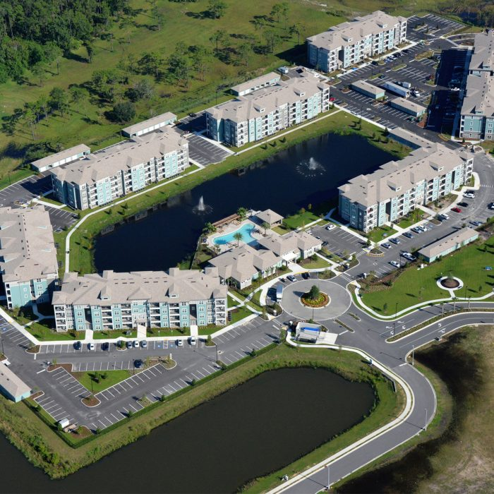 Multi story apartment complex with pond and fountains aerial shot