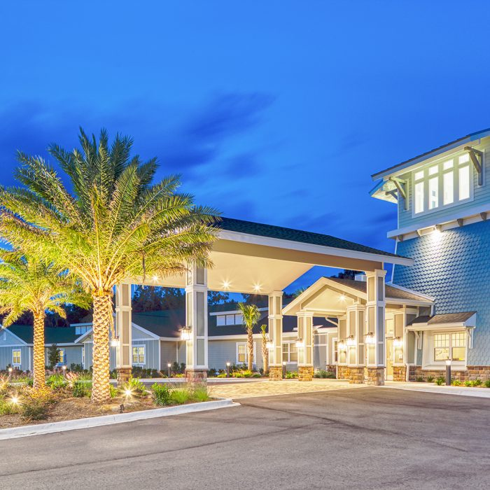 Evening view of a blue senior living facility with multiple rooms and a grand entryway