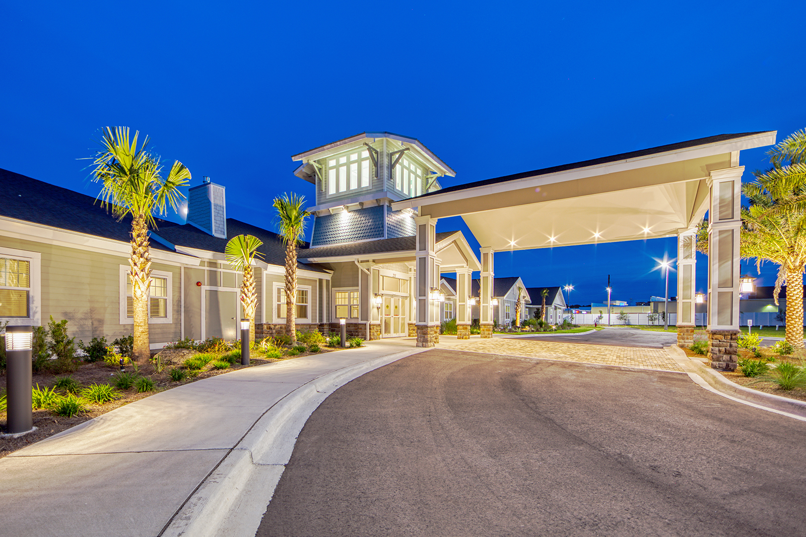 Senior living facility with palm trees entrance at evening