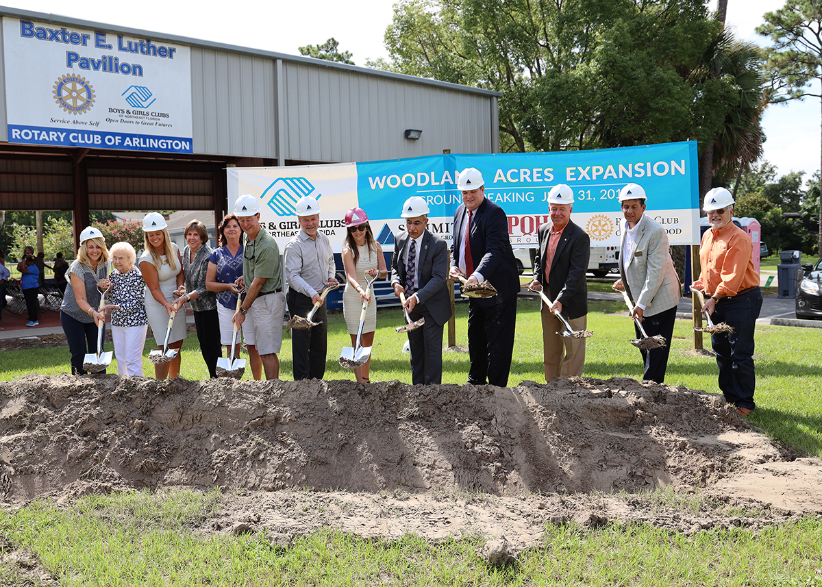 Summit employees in professional attire digging dirt at new construction site