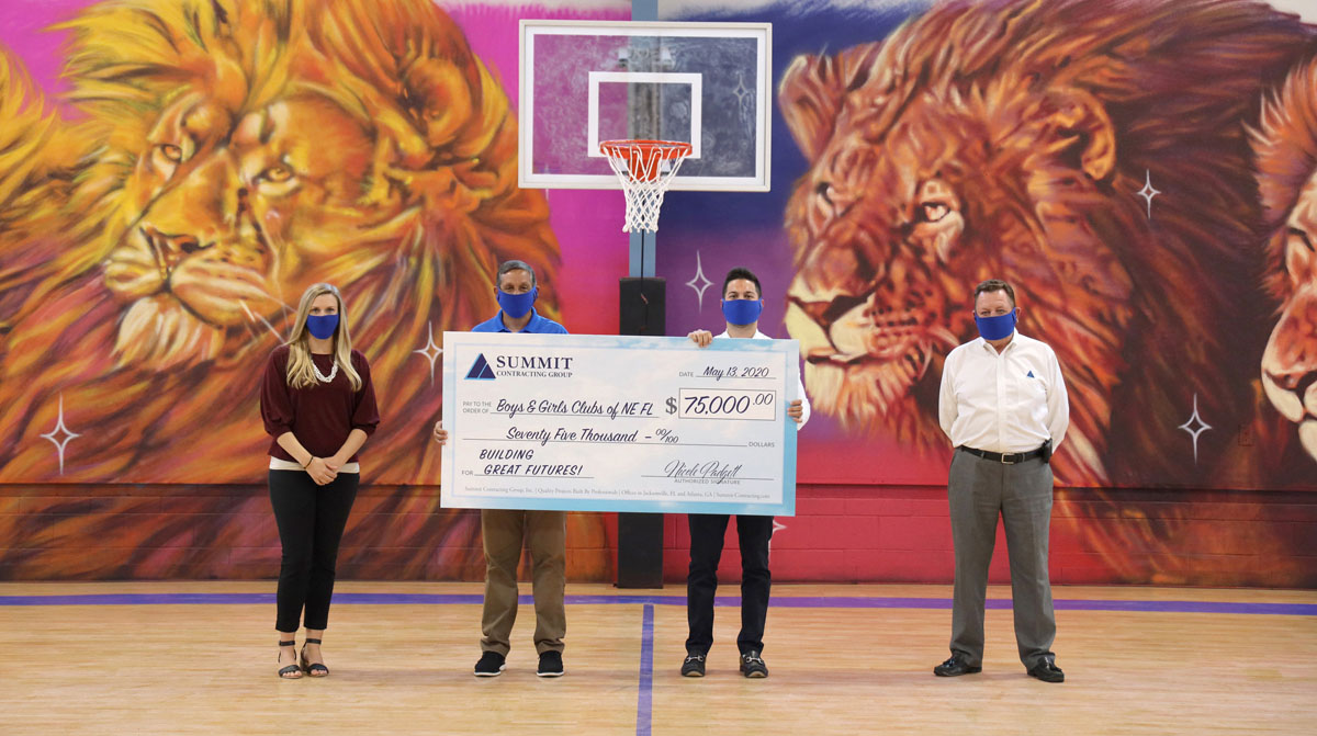 people standing in a gym holding a large check