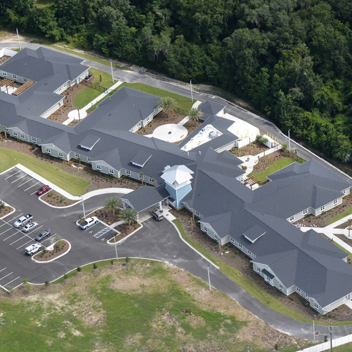 Aerial view of senior living facility with multiple living quarters and palm trees