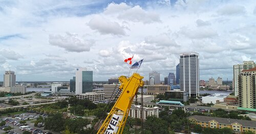Crane with flags in front of Jacksonville's downtown