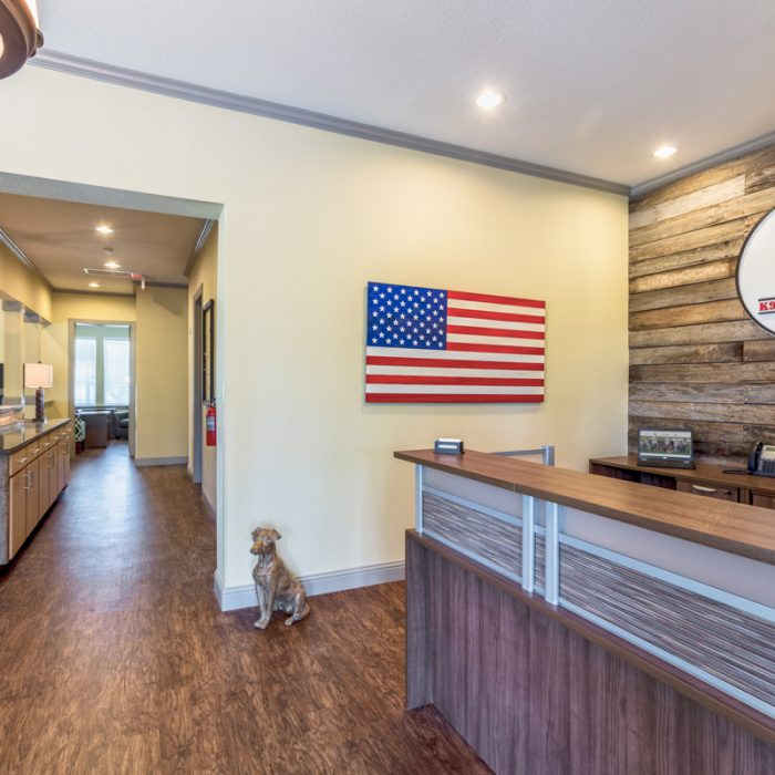 Front desk with American flag and logo plaque at K9s For Warriors Project by Summit Contracting Group