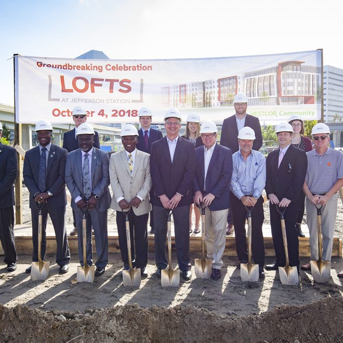 Executives and contractors smiling with shovels at new development ground
