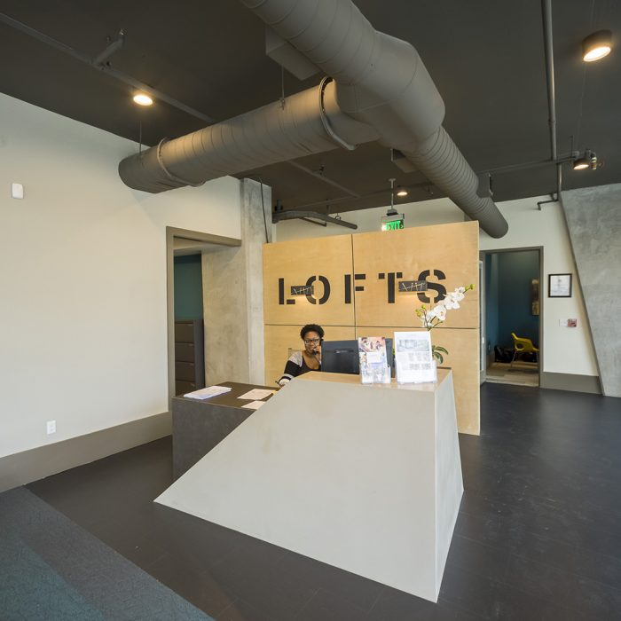 Smiling receptionist with Lofts sign behind her