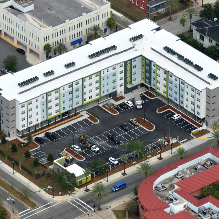 Multi story apartment complex with parking lot aerial view
