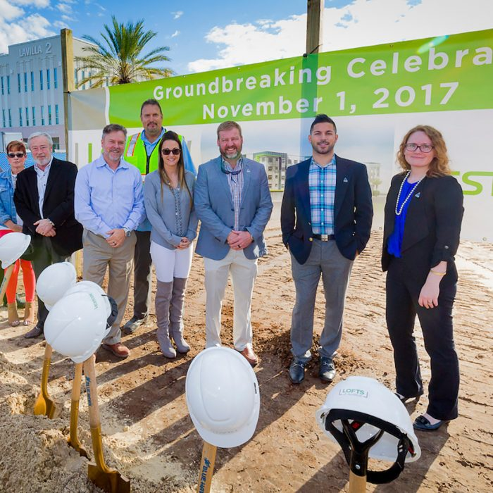 Executives and contractors smiling with shovels at new site