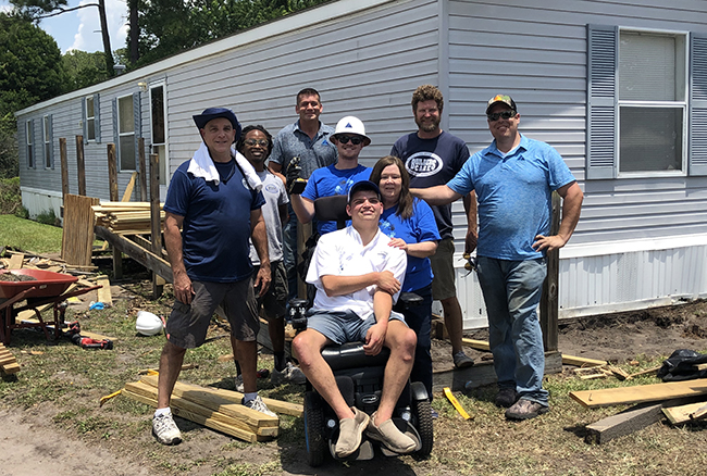 Summit employees working on site with man in wheelchair in front of trailer home