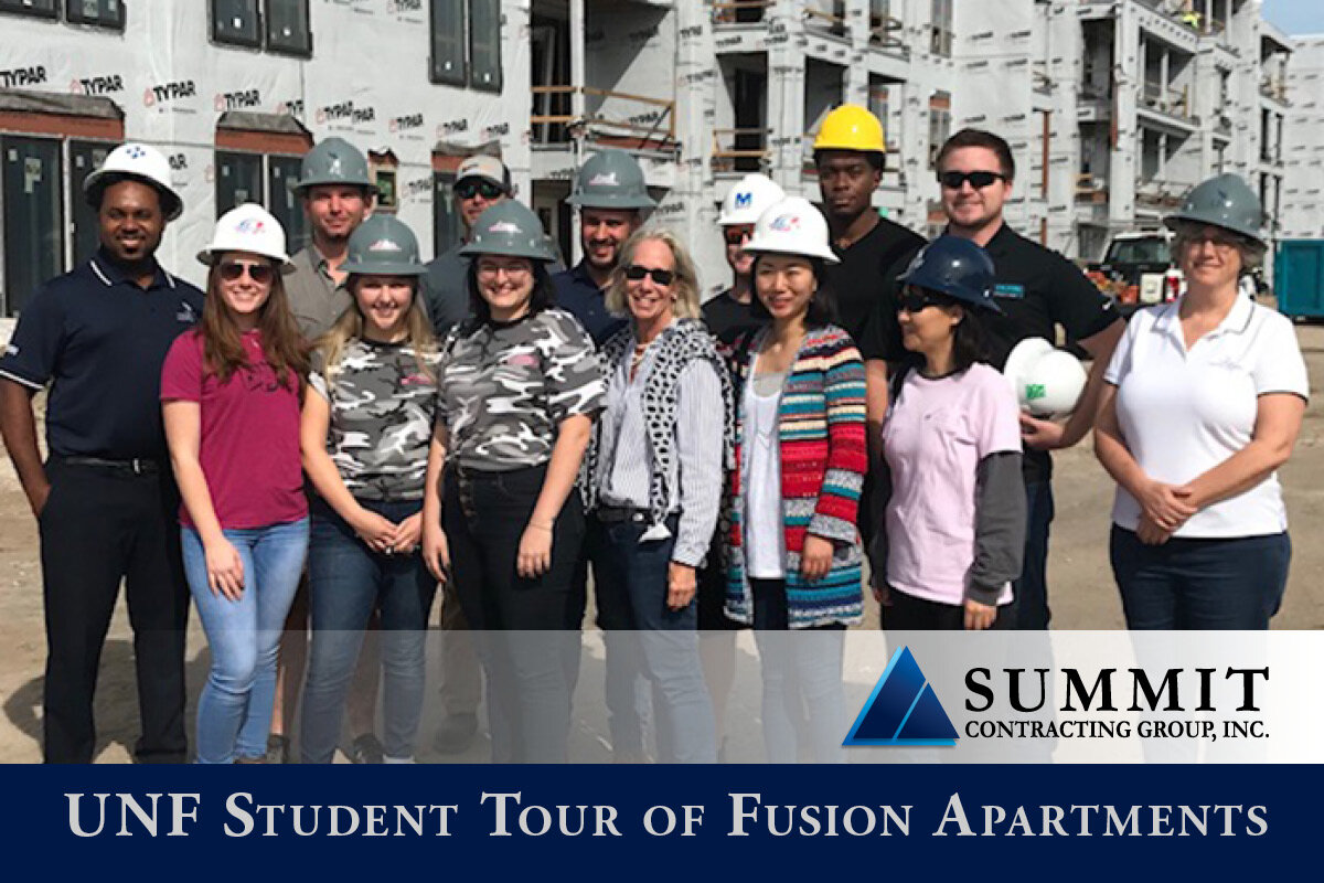 Students and Summit employees in hard hats at construction site