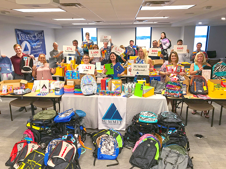 Backpacks and school supplies collected by Summit employees holding signs with data - 274 backpacks, 1,400 pencils, 2,368 crayons, 1,521 pens, 800 markers, 600 erasers, 57 scientific calculators collected by Summit Contracting Group