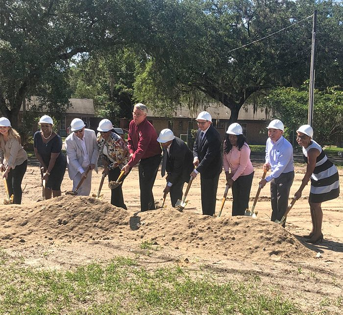 Group of executives and contractors digging into ground for new development