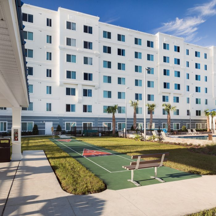 Madison Crossing Market Rate Senior Living Apartments view of building with pool and sports area