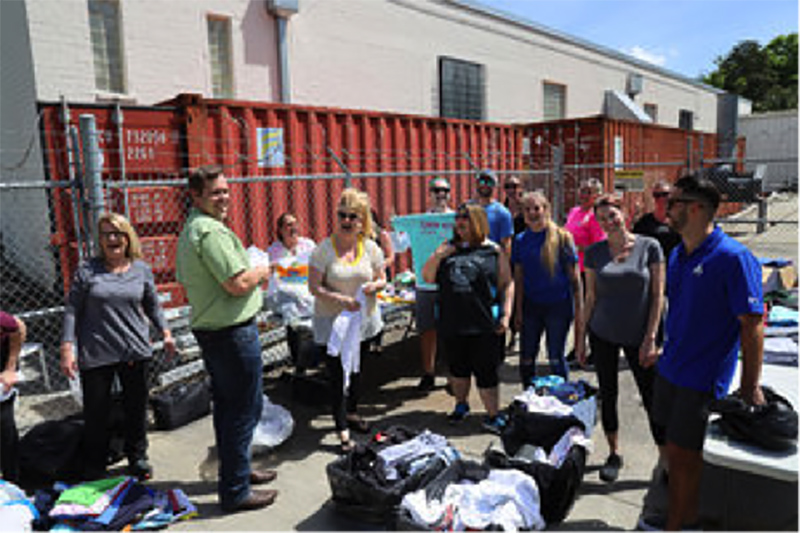 Photo of volunteers sorting shirts at Uplifting Volunteer Day by Summit Contracting Group