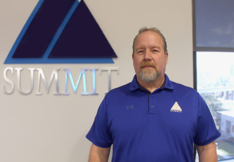 Portrait of Tom Born in front of Summit Logo