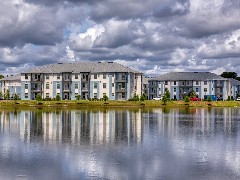 3 story apartment building across a lake