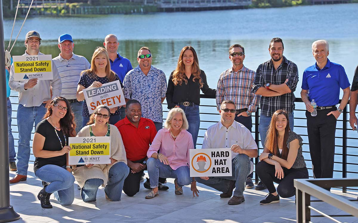 group of people posing on a deck holding signs
